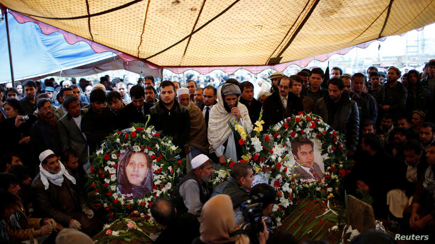 Pictures of Afghan journalist Sardar Ahmad of Agence France-Presse (R) and his wife are placed on their graves in Kabul March 23, 2014.