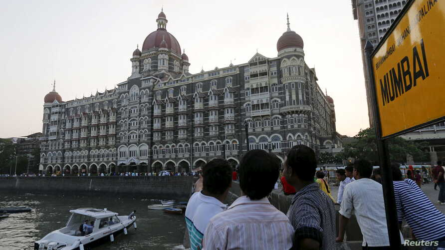 Tourists are seen in front of the Taj Mahal hotel, which was one of the targets of the Nov. 26, 2008 attacks, in Mumbai April 10, 2015.