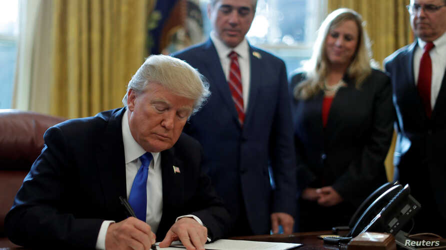 """U.S. President Donald Trump signs an Executive Order on """"Supporting our Veterans during their Transition from Uniformed Service to Civilian Life"""" in the Oval Office of the White House in Washington, Jan. 9, 2018."""