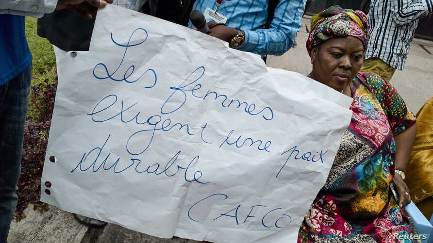 "FILE - A Congolese woman holds a placard saying ""Women require stable peace"" as she and others sit in protest during talks between the opposition and the government of President Joseph Kabila outside the Conference episcopale nationale du Congo (CENC"