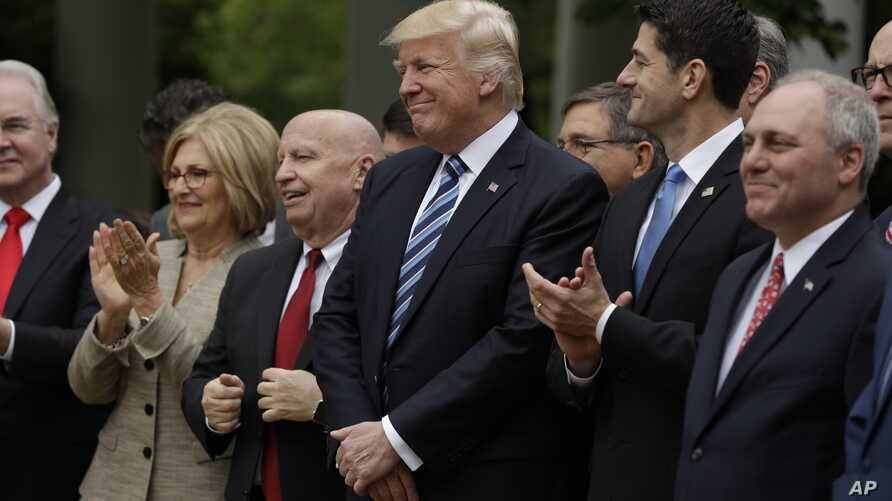 President Donald Trump, flanked by House Ways and Means Committee Chairman Rep. Kevin Brady, R-Texas, and House Speaker Paul Ryan of Wisconsin, are seen  in the Rose Garden of the White House in Washington after the House approved a health care bill,