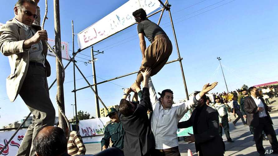 Men prevent execution of convict pardoned by family of policeman he was convicted of killing, Mashhad, northeastern Iran, May 8, 2013.