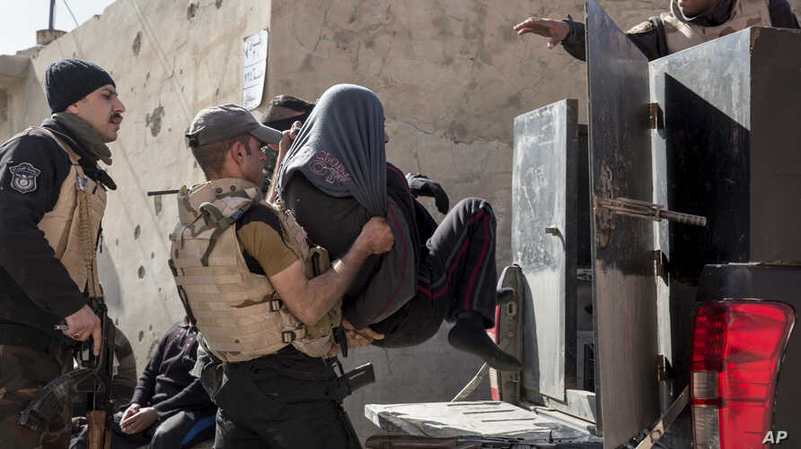 Iraqi security officers place a suspected Islamic State group member into the back of a waiting pickup truck, in east Mosul, Feb. 21, 2017.
