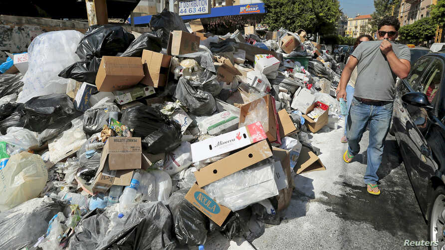 A man covers his nose as he walks past a pile of garbage along a street in Beirut, Lebanon, July 22, 2015.