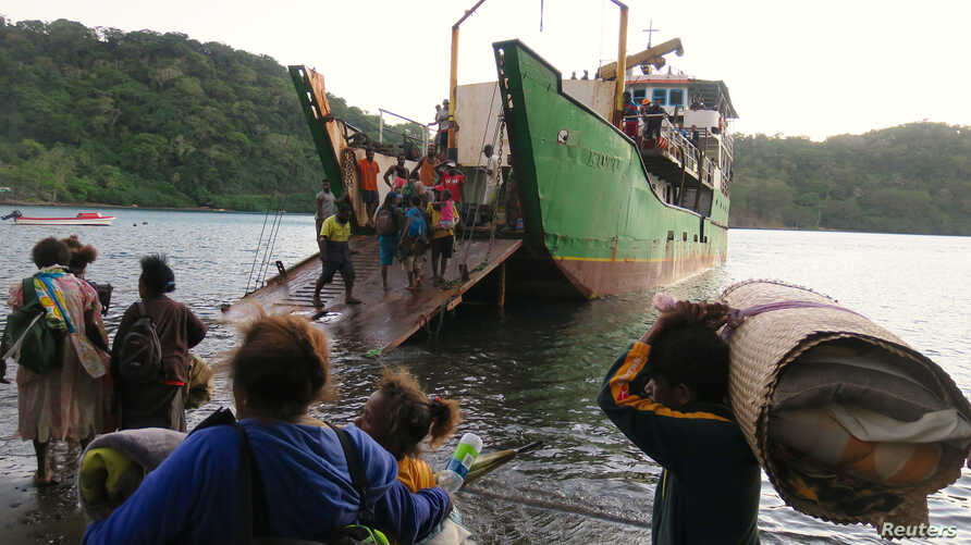 FILE - Residents carrying their possessions aboard a boat at Lolowai Port as they evacuate because of the Manaro Voui volcano continuing to belch smoke and ash on Vanuatu's northern island of Ambae in the South Pacific, Oct. 1, 2017.