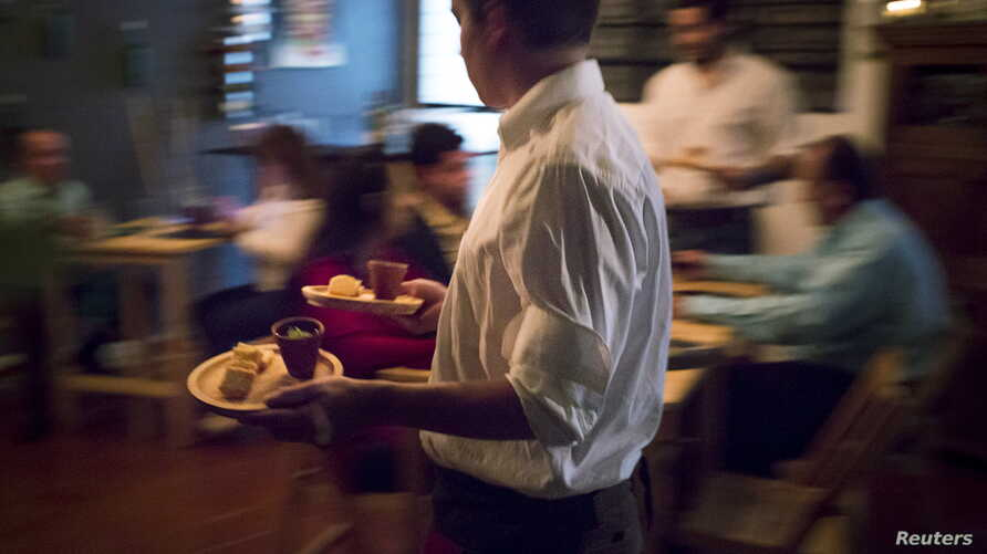"""A waiter carries dishes for diners at the """"Ciboulette Prive"""" in Caracas, Venezuela, June 9, 2015."""