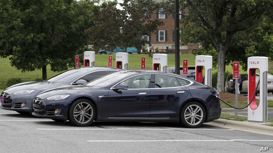 Telsa cars recharge at a Tesla station at a shopping center in Charlotte, N.C., June 24, 2017. Buyers of Tesla's luxury models have access to a company-funded Supercharger network.