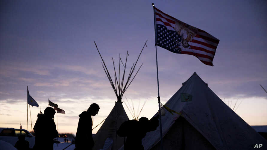FILE - In this Dec. 2, 2016, file photo, travelers arrive at the Oceti Sakowin camp where people have gathered to protest the Dakota Access oil pipeline as they walk into a tent next to an upside-down american flag in Cannon Ball, N.D.