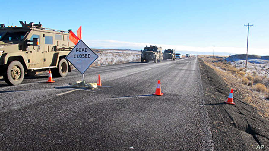 A convoy of armored vehicles and SUVs rolls past a barricade on the road near the Malheur National Wildlife Refuge near Burns, Ore., Jan. 30, 2016.