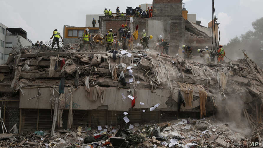 Workers shovel papers and debris off the top of the rubble of a building that collapsed in last week's 7.1 magnitude earthquake, at the corner of Gabriel Mancera and Escocia streets in the Del Valle neighborhood of Mexico City, Monday, Sept. 25, 2017