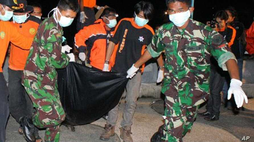 Rescuers carry the newly recovered body of a victim of the collapse of Kutai Kartanegara bridge in Tenggarong, East Kalimantan, Indonesia, November 29, 2011.