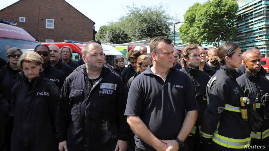 Members of the emergency services attend a minute's silence for the victims of the Grenfell Tower fire near the site of the blaze in North Kensington, London,  June 19, 2017.
