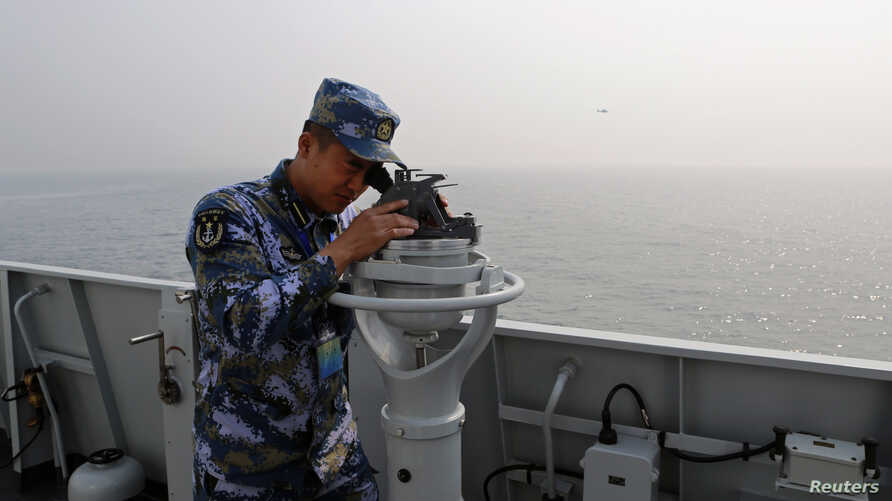 Chinese naval sailor monitors sea conditions on board Chinese frigate Linyi during multi-country maritime joint exercises off the coast in Qingdao, Shandong province, April 23, 2014.