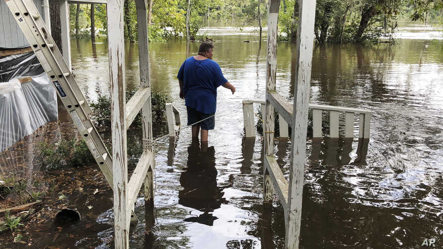Shawn Lowrimore, Pastor Willie Lowrimore of The Fellowship With Jesus Ministries', son, wades into water near the church in Yauhannah, S.C., on Sept. 24, 2018.