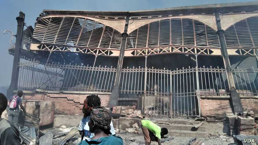 People stand in front of fire-damaged Iron Market in Port-au-Prince, Haiti, Feb. 13, 2018. (F. Lisené/VOA Creole)