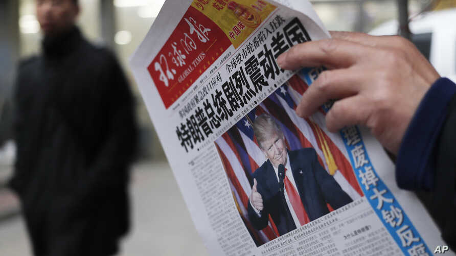 A man reads a newspaper with the headline of 'U.S. President-elect Donald Trump delivers a mighty shock to America' at a news stand in Beijing.