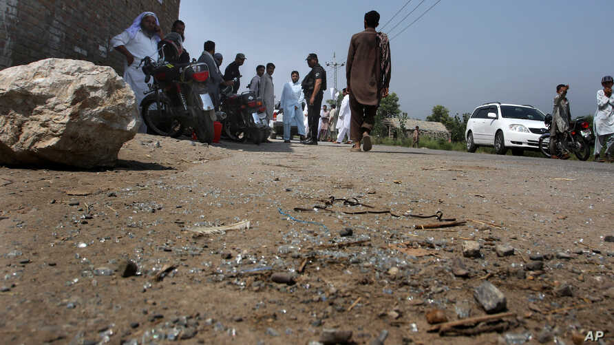 Pakistani police officers and local residents gather at the site of firing incident at Garhi Sohbat Khan on the outskirts of Peshawar, Sept. 18, 2016.
