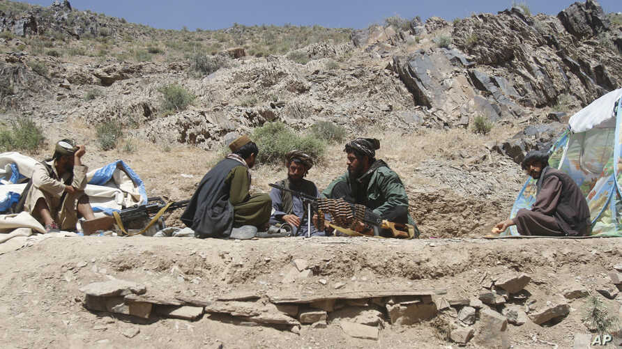 In this May 27, 2016, photo, Taliban fighters eat lunch in Shindand district of Herat province, Afghanistan.