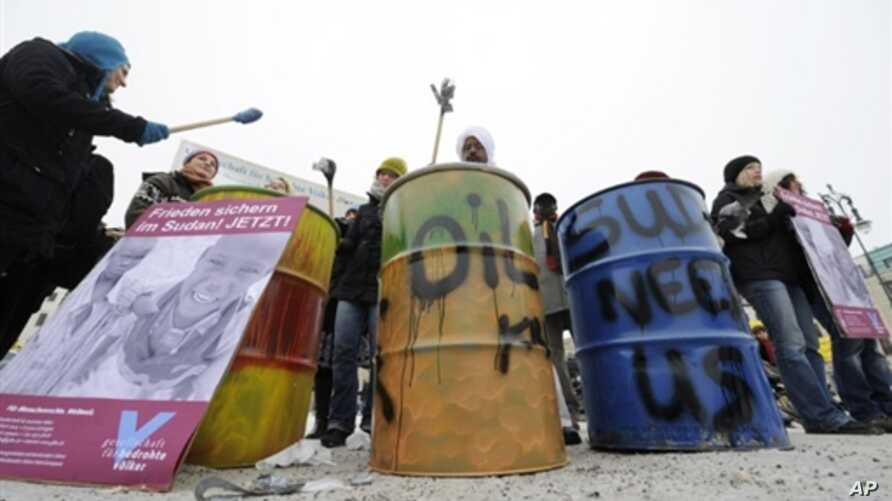 Activists bang oil drums during a protest by human rights advocates Amnesty International, to call attention to the allegedly worsening situation in Sudan, in Berlin 7 Jan 2010