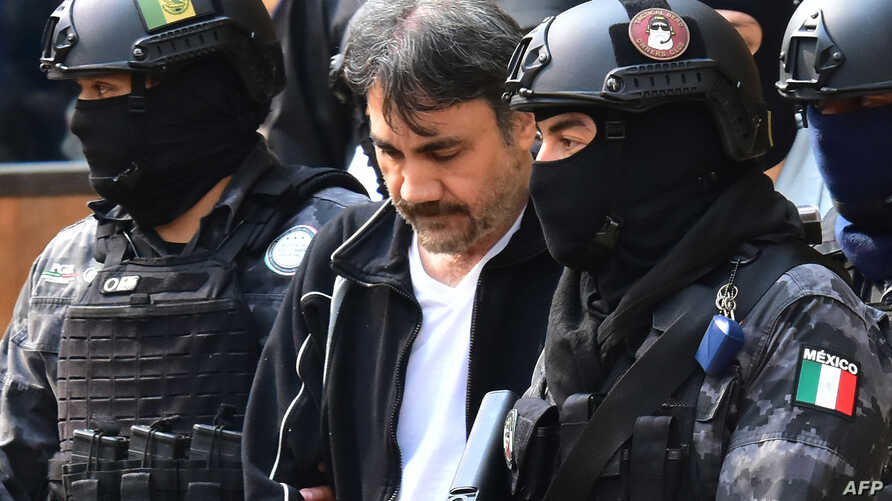 "FILE - Agents of the Criminal Investigation Agency and soldiers of the Mexican army escort Damaso Lopez, a senior lieutenant of drug lord Joaquin ""Chapo"" Guzman, in Mexico City, May 2, 2017."