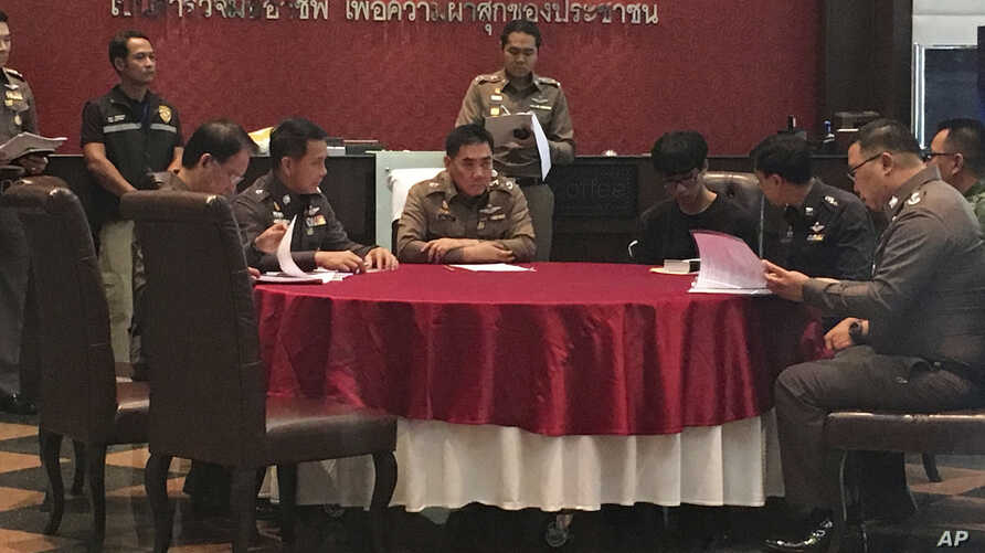 Natdanai Kongdee, third from right, is interviewed at the police headquarters in Bangkok, Thailand, Dec 26, 2016.