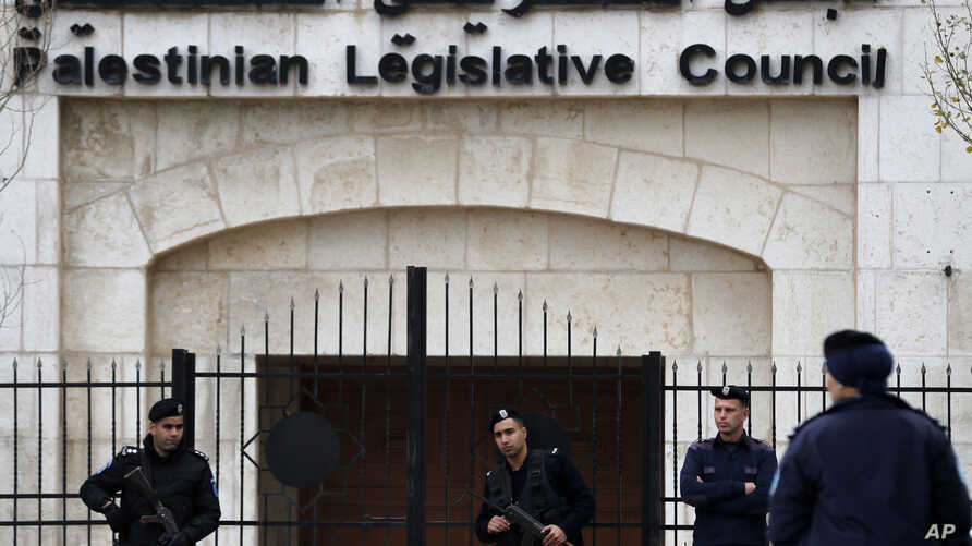 FILE - Palestinian security forces are seen in front of the Palestinian Legislative Council building in Ramallah, in the Israeli-occupied West Bank, Dec. 26, 2018.