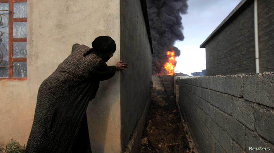 A woman looks at fire and smoke from oil wells set ablaze by Islamic State militants before the fled the oil-producing region of Qayyara, Iraq, Nov. 4, 2016.