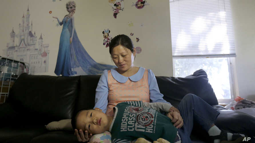 Liu Xiaodong, the wife of prominent Chinese dissident Zhao Changqing, holds her son Yaokun Zhao as they are interviewed in Hayward, Calif., Wednesday, July 20, 2016.
