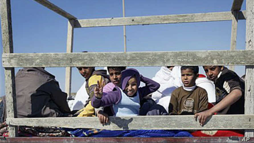 Children sit in the back of an open-air truck as they flee Brega during an exchange of fire with pro-Gadhafi forces, in Libya, April 4, 2011