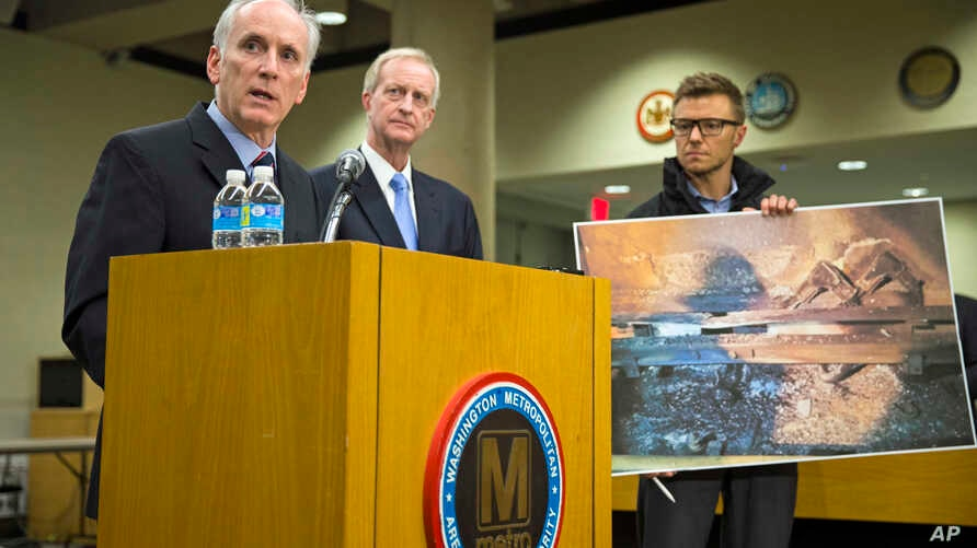 An aide to Metro General Manager Paul Wiedefeld (l) holds up a photo of a track damaged by fire as Wiedefeld speaks during a news conference to announce that the DC Metrorail service will be shut down for a full day, at the Washington Metropolitan Ar