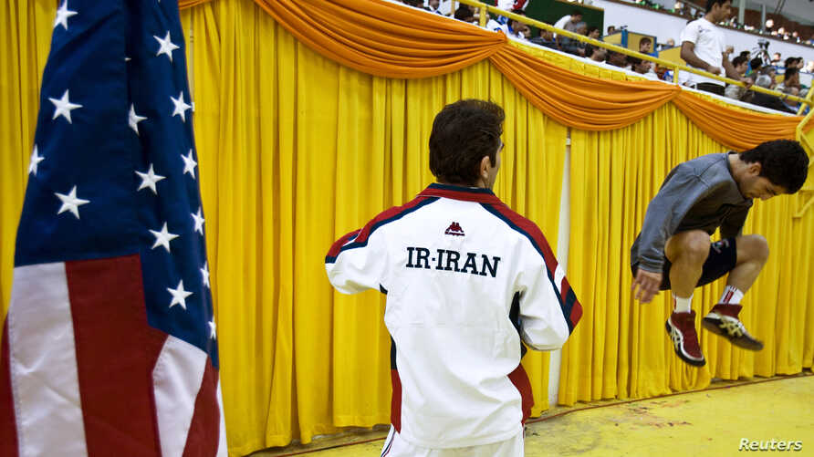 FILE - An Iranian wrestler warms up beside an American flag before his match during the 2009 Takhti Free Style Wrestling Tournament in Tehran.