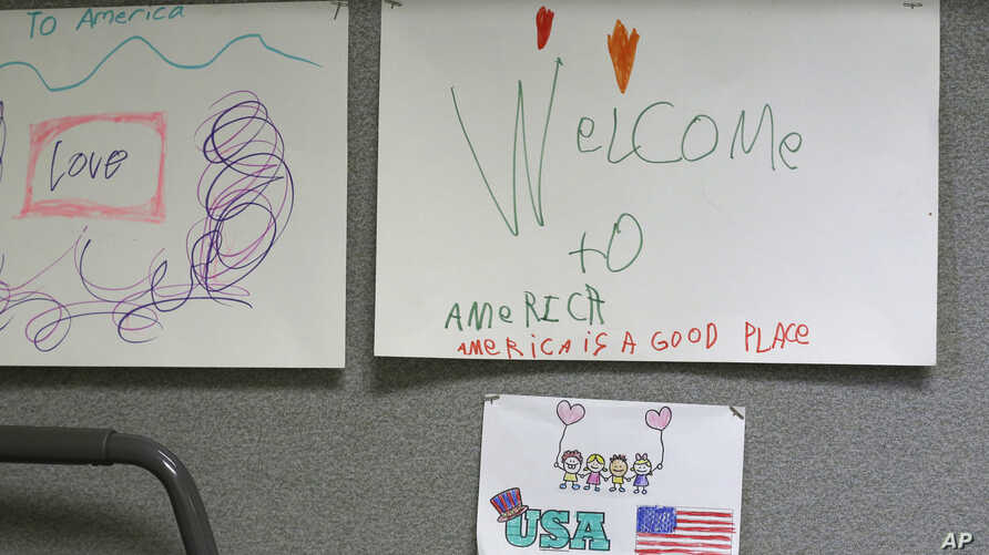 "Children's drawings that read ""Welcome to America, America is a good place,"" are displayed April 24, 2017, at a Jewish Family Service Refugee and Immigrant Service Center in Kent, Wash., during a visit by Washington Gov. Jay Inslee."