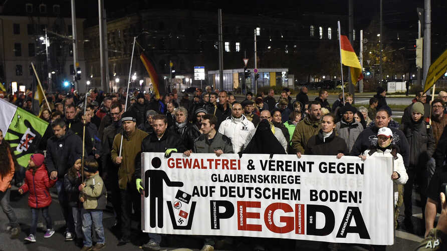 """FILE - Protesters hold a banner reading """"Without violence and united against religious wars on German soil - Pegida"""" during a rally in Dresden, eastern Germany, Nov. 2, 2015."""