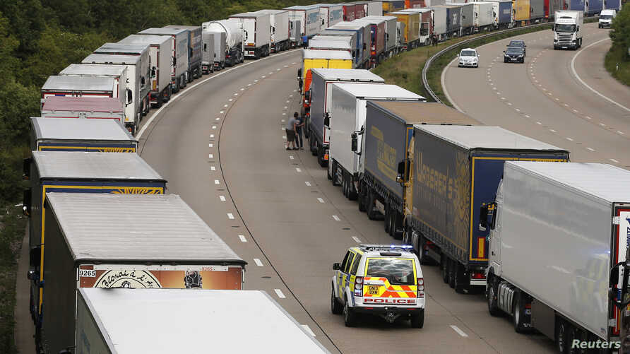 A police vehicle drives past lorries are backed up on the M20 motorway which leads from London to the Channel Tunnel terminal at Ashford and the Ferry Terminal at Dover,  June 23, 2015. The Channel Tunnel terminal and ferry port at Calais were both s