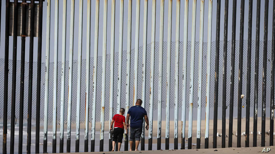 Two people walk towards metal bars marking the United States border where it meets the Pacific Ocean, March 2, 2016, in Tijuana, Mexico.