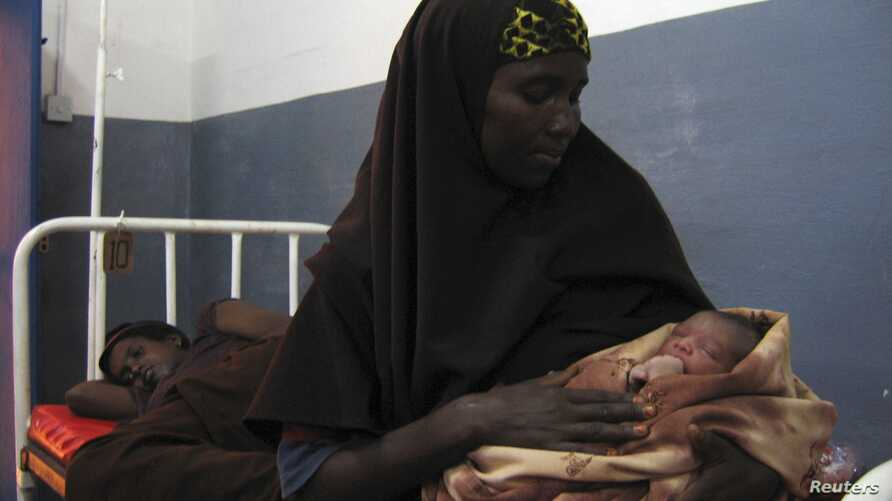 Somali woman holds a newly born baby at a hospital run by Doctors Without Borders, Jowhar, north of Mogadishu, Aug. 3, 2007.