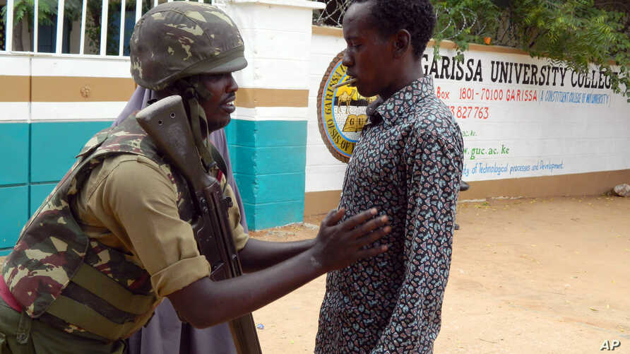 An armed security officer checks a student entering the Garissa university college, in Garissa, Kenya, on Jan. 4, 2016.