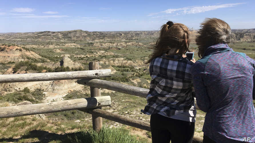 Jeanne Randall and her daughter Zoe, of Shoreview, Minn., take photos at Painted Canyon in Theodore Roosevelt National Park in western North Dakota, May 24, 2017. A company wants to build an oil refinery about 3 miles from the park, but some worry ab