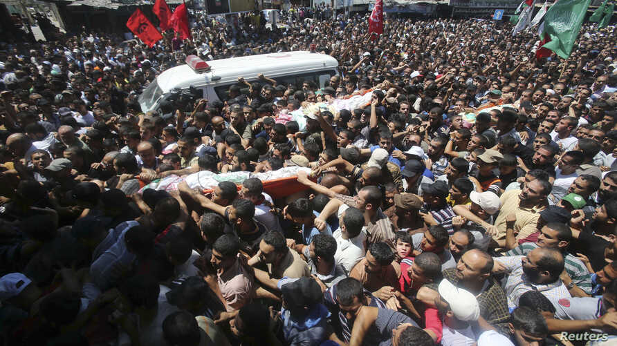 Palestinians carry the bodies of three senior Hamas commanders, who were killed in an Israeli air strike, during their funeral in Rafah in the southern Gaza Strip, Aug. 21, 2014.