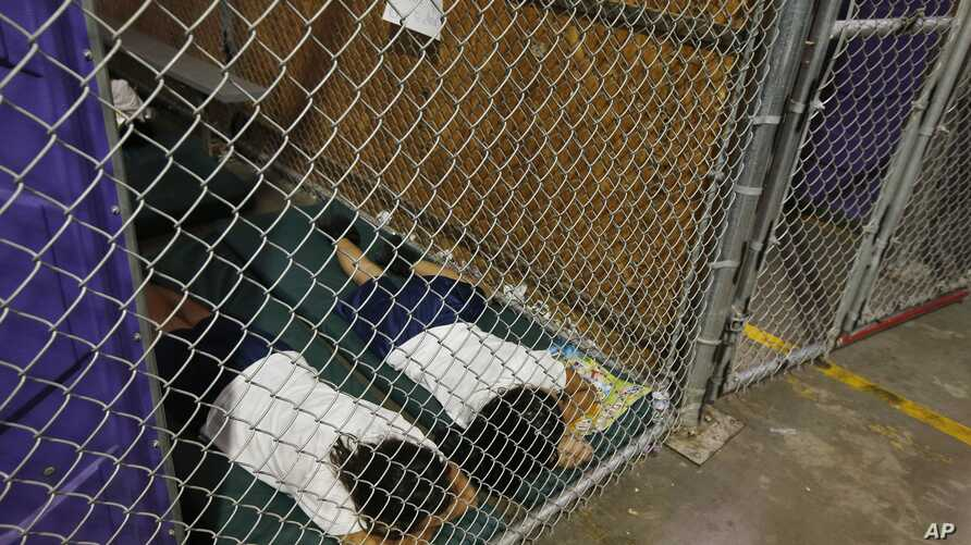Two female detainees sleep in a holding cell, as the children are separated by age group and gender, as hundreds of mostly Central American immigrant children are being processed and held at the U.S. Customs and Border Protection Nogales Placement Ce