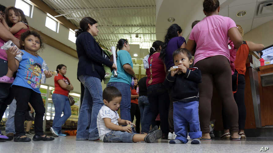 FILE - Immigrants who entered the U.S. illegally stand in line for tickets at the bus station after they were released from a U.S. Customs and Border Protection processing facility in McAllen, Texas.