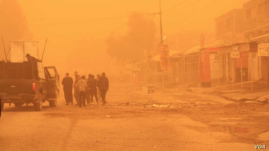 Despite the fog increasing the danger of IS militants launching attacks in Iraqi areas, families stop soldiers to ask where to find humanitarian aid on Dec. 2, 2016 in Mosul, Iraq. (H.Murdock/VOA)