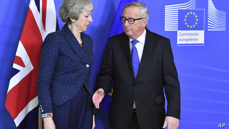 European Commission President Jean-Claude Juncker, right, prepares to shake hands with British Prime Minister Theresa May, left, before their meeting at the European Commission headquarters in Brussels, Belgium, Feb. 7, 2019.