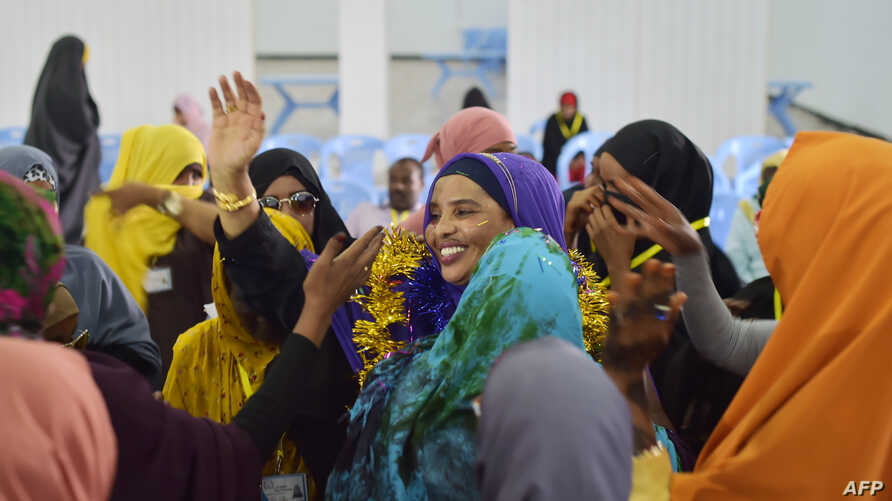 A handout picture released by the African Union-United Nations Information Support Team, shows Yurub Ahmed Raabi, the winner of a seat in the Somalia's parliament (House of the People), celebrating with delegates who voted for heat a polling station