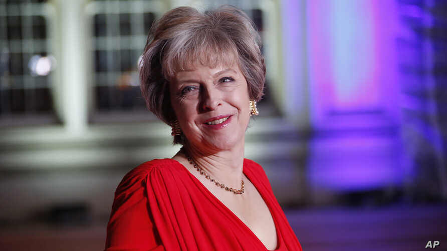 FILE - Britain's Prime Minister Theresa May poses for photographers upon arrival at The Sun Military Awards 2016 in London.