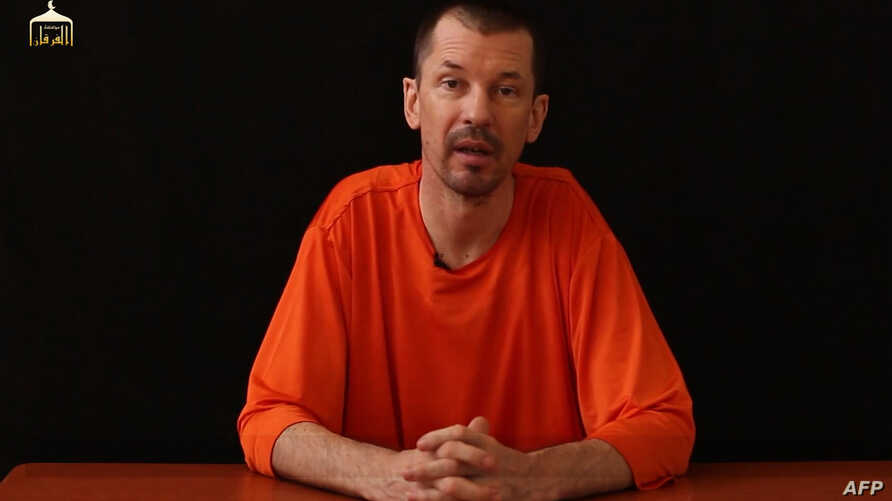 An image taken from a video released by the Islamic State (IS) group through Al-Furqan Media via YouTube allegedly shows British freelance photojournalist, John Cantlie, at an undisclosed location in which he says he is being held captive, Sept. 18, ...