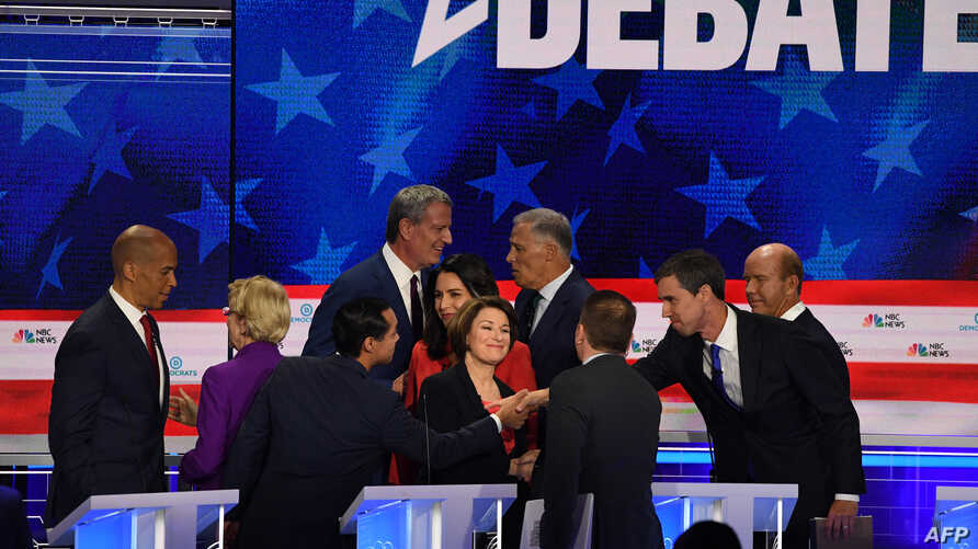 Democratic presidential hopefuls, left to right, Cory Booker, Elizabeth Warren, Julian Castro, Bill de Blasio, Tulsi Gabbard,  Amy Klobuchar,  Jay Inslee, moderator Chuck Todd, Beto O'Rourke and John Delaney greet each other at the end of the first night of the Democratic presidential primary debate in Miami, June 26, 2019.