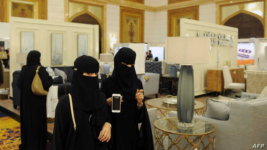 FILE - Saudi women wear the mandatory abaya, or loose-fitting gown, over their clothes in Jeddah, Saudi Arabia, Nov. 8, 2017. Rumors are circulating that a mixed-gender nightclub that does not require women to wear loose robes has opened in the city.
