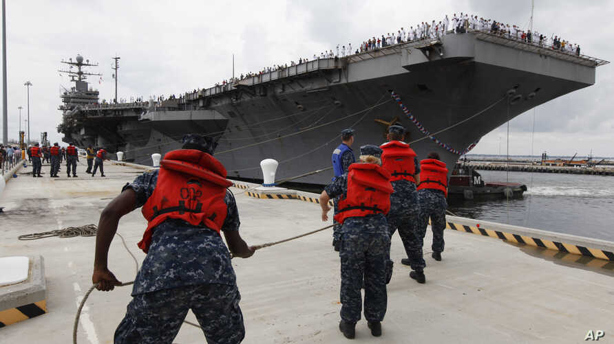 "FILE - Navy shore crew haul in lines as the USS Abraham Lincoln arrives at Naval Station Norfolk in Norfolk, Va., Aug. 7, 2012. The U.S. has dispatched the USS Abraham Lincoln and other military resources to the Middle East following ""clear indicat..."