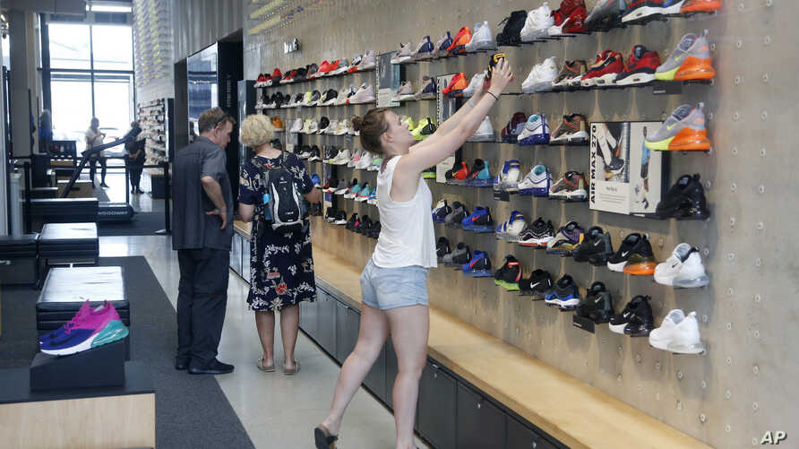 FILE - Shoppers look at shoes at the Nike Miami store on the Lincoln Road Mall in Miami Beach, Fla., Sept 4, 2018. The sneaker seller will launch a foot-scanning tool on its app this summer that will measure and remember the length, width and other d...